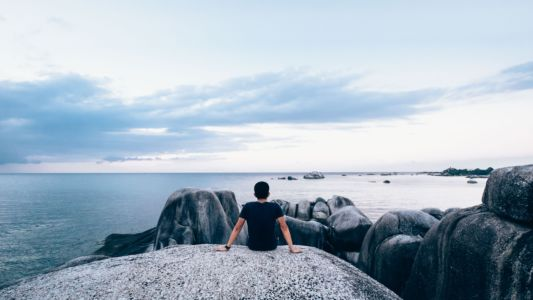 Man sitting by the ocean